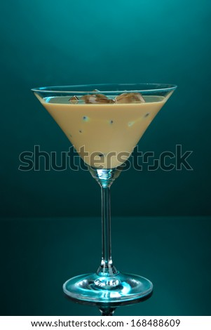Baileys liqueur in glass on blue background - stock photo