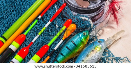 bait, wobbler and fishing accessories on wooden background