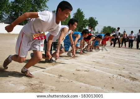 BAIXING COUNTY, CHINA - MAY 12, 2011: Baixiang County Middle School Track Meet held in May 12, 2011. Unidentified student athletes struggling after hearing the starting signal toward the front. - stock photo