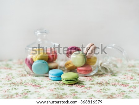 Bake delicious colorful macaroons stored in glass jars. - stock photo