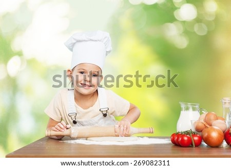Bake. Happy little chef smeary with flour stretching the dough - stock photo