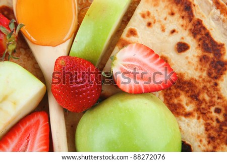 baked and fruits : pancake with honey strawberries and apple isolated over white background on wooden plate