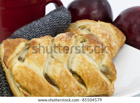 Baked apple strudel placed on white plate, black tweed napkin, with red mug and red fruit behind