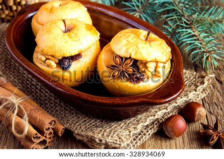 baked apples stuffed with dried fruit, nuts and honey in rustic ceramic dish with cinnamon, anise stars and pine branches over wooden background - stock photo