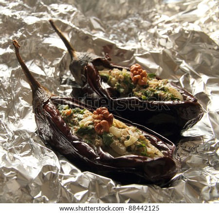 Baked aubergines stuffed with walnut filling on foil - stock photo