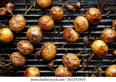 Baked baby potatoes in the form skewers on grill pan - stock photo