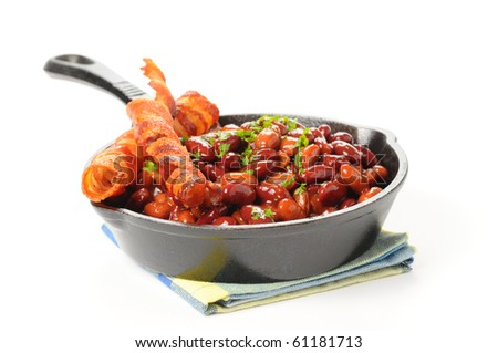 Baked beans and bacon served in a cast iron skillet. - stock photo