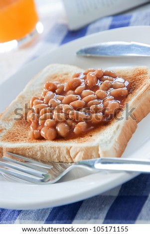 Baked beans on a slice of toasted bread on a white plate with breakfast table setting - stock photo