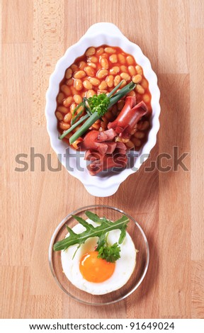 Baked beans with grilled Bohemian sausages and fried egg - stock photo