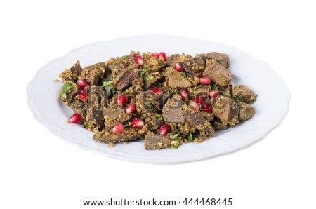 Baked beef liver with walnuts and pomegranate seeds. Georgian cuisine. Isolated on a white background.