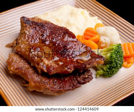 Baked beef steak serving with cooked vegetable - stock photo