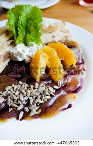 Baked beetroot salad with cheese and oranges, closeup