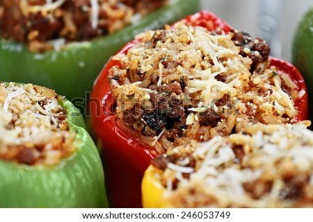 Baked bell peppers stuffed with beef, rice, vegetables and cheese with extreme shallow depth of field. - stock photo