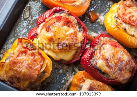 Baked bell peppers stuffed with chopped meat on black baking pan - stock photo