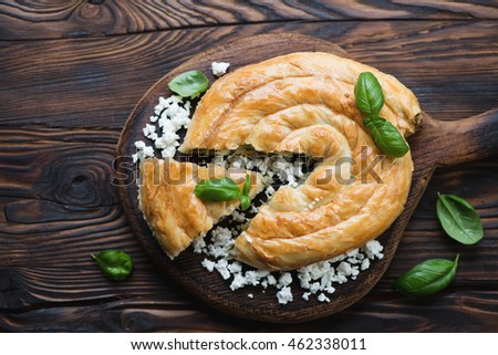 Baked burek pie in a rustic wooden setting, above view