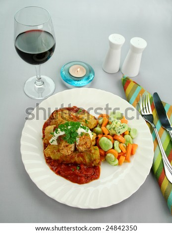 Baked cabbage rolls with carrots and broad beans with a tomato sauce. - stock photo