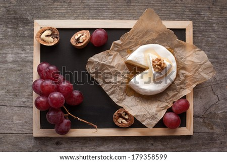Baked Camembert cheese with honey, nuts and grapes on wooden background - stock photo
