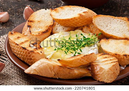 Baked Camembert cheese with thyme and toast rubbed with garlic - stock photo