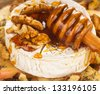 Baked camembert with apples dipped with honey and walnuts - stock photo