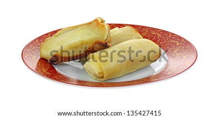 Baked  cheese blintzes on a red and gold decorative plate.