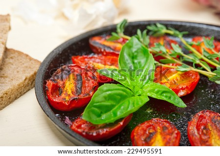baked cherry tomatoes with basil and thyme - stock photo