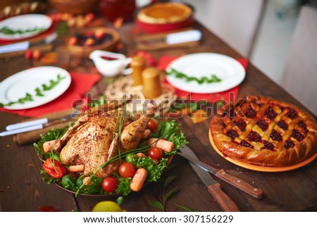 Baked chicken and berry pie on table - stock photo