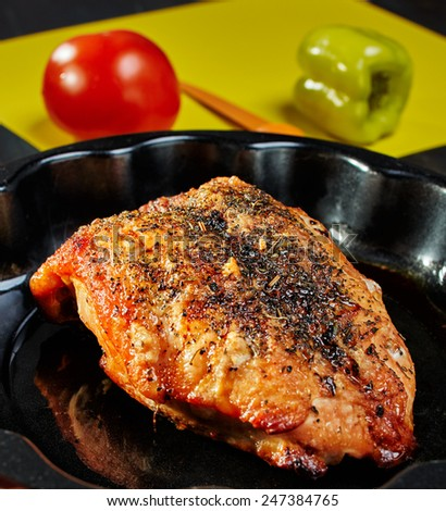 Baked chicken breast in a baking dish. Tomato and pepper with a knife on a yellow cutting board.