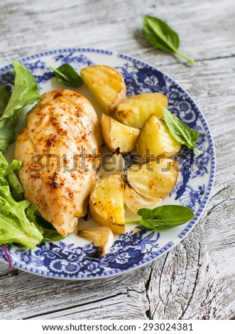 baked chicken breast with potatoes and onions on a vintage plate on a light wooden background - stock photo