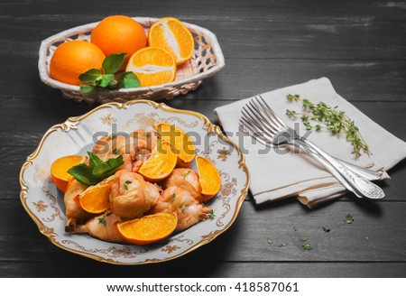 Baked chicken drumstick with baked oranges, fresh oranges cut for chicken, green mint, thyme, silver fork, a white porcelain plate, cloth, wicker basket on a dark black wooden rustic background - stock photo