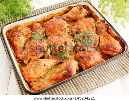 Baked chicken drumsticks on a baking tray - stock photo