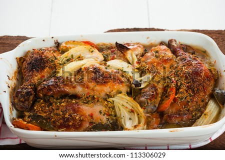 baked chicken drumsticks with vegetables in white casserole - stock photo