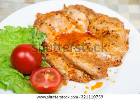 Baked chicken fillet in a spicy sauce with tomato and leaf salad