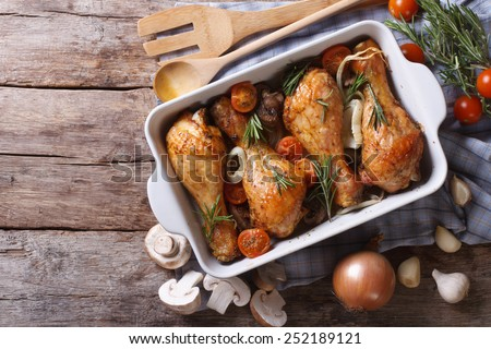 Baked chicken legs with mushrooms and vegetables. horizontal view from above  - stock photo