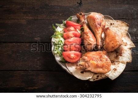 Baked chicken meat and tortilla bread served in plate,blank space on wooden background  - stock photo
