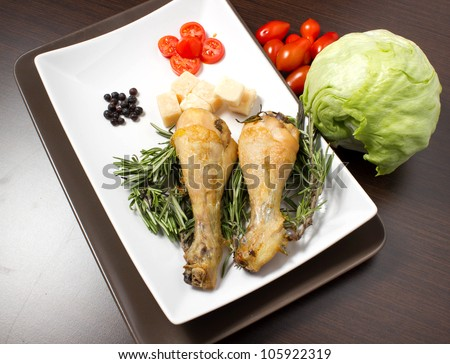 Baked chicken on the table with spices and vegetables