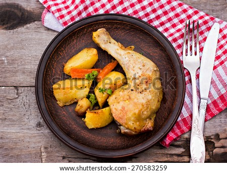 Baked chicken pieces with potatoes, herbs and garlic on a wooden table - stock photo
