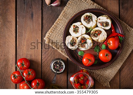 Baked chicken rolls with mushrooms and paprika on brown plate. Top view - stock photo
