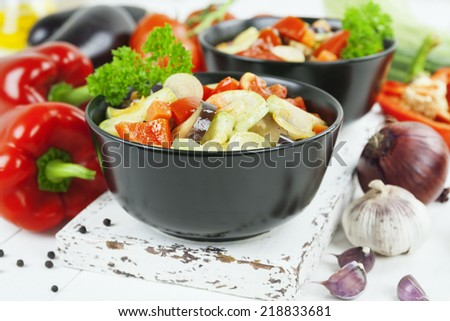 Baked colourful vegetables in the ceramic pot on the wooden table