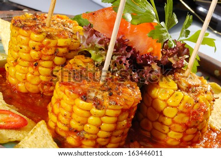 Baked corn with salsa and tortilla chips - stock photo