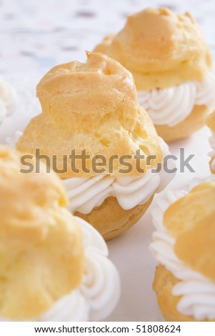 Baked cream puffs filled with pastry cream. - stock photo