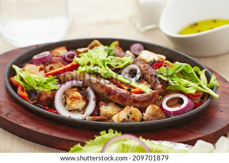 baked diced chicken and sausage with onions, peppers, mushrooms and a salad of tomatoes, mushrooms, peppers and lettuce. - stock photo