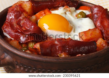 baked eggs with chorizo and potatoes in a pot. macro horizontal