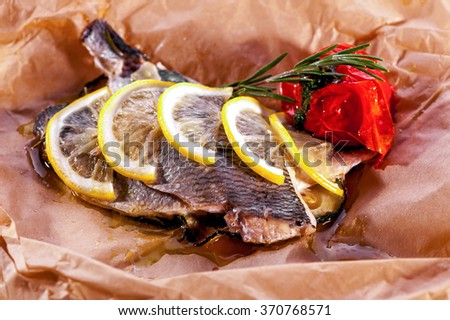baked fish close-up decorated with lemon and rosemary served on parchment paper  - stock photo