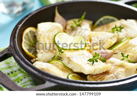 Baked fish fillet with lemon, lime, garlic and themy - stock photo