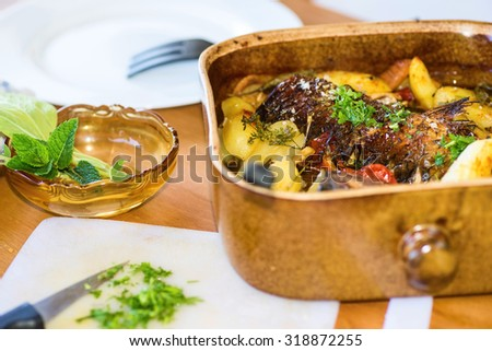 Baked fish in old rustic ceramic pan with potatoes and herbs