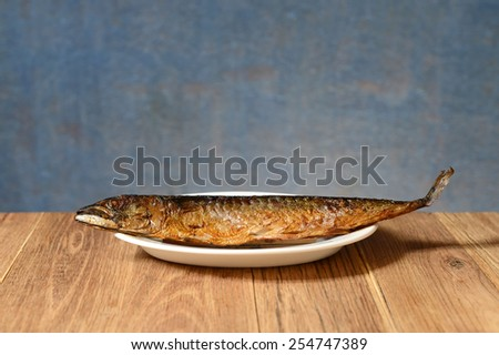 Baked fish mackerel in a plate on the table - stock photo