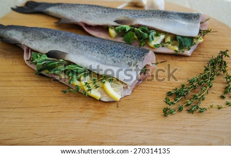 Baked fish Rainbow Trout Stuffed with herbs on a Cutting board - stock photo