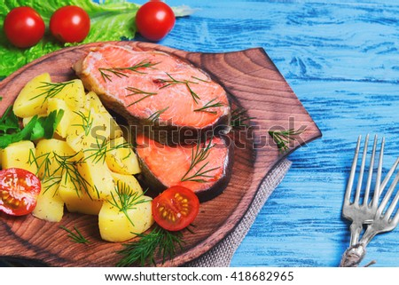 Baked fish with potatoes salmon steak fillet red fish, potato slices, parsley, dill, lettuce, cherry tomatoes on sacking on a blue wooden background - stock photo
