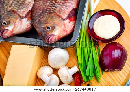 Baked fish with vegetables, sauce, red pepper on cutting board - stock photo