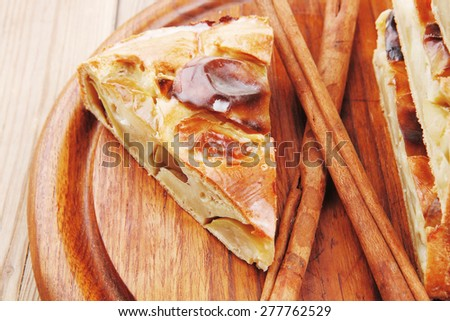 baked food : apple pies on wooden plate over table with cinnamon sticks - stock photo